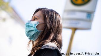 Женщина в медицинской маске на остановке общественного транспорта в Берлине