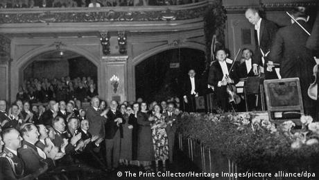 Links uniformierte Parteimitglieder, die applaudieren. Rechts auf der Bühne verbeugt sich Wilhelm Furtwängler.