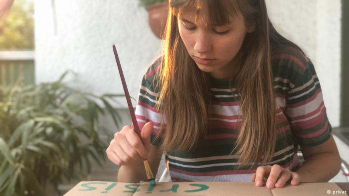 Actvist Pauline Brünger paints a protest poster for the digital climate strike