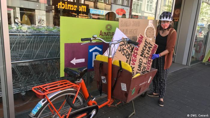Lena Müllhäuser von Parents for Future Köln mit ihrem Lastenrad vor einem einem Bio-Supermarkt in Köln
