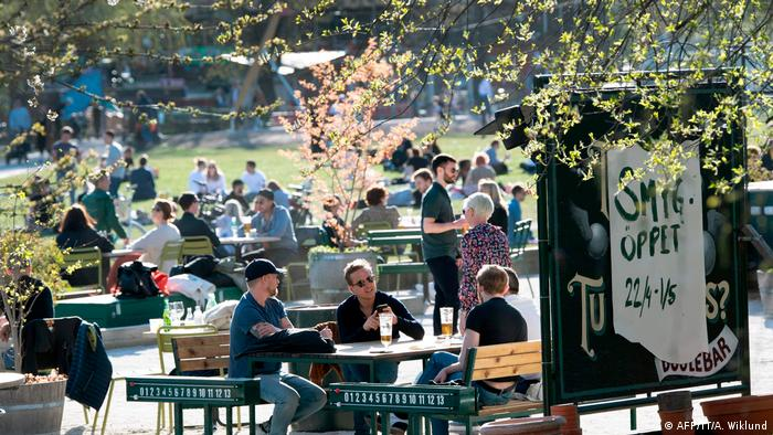 People enjoy warm and spring-like weather with high temperatures on a cafe terrace