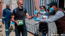 Cleveland Civic Committee volunteers distributes hot meals and sanitiser during a food distribution in Cleveland, near Johannesburg, on April 20, 2020. - Despite the promise by South African Social Development minister Lindiwe Zulu to increase food aid deliveries, the role played by the private charity sector remain crucial. (Photo by Luca Sola / AFP)