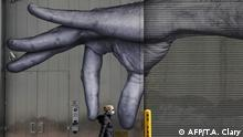 TOPSHOT - A woman in a mask walks past a mural of a hand on the side of a building in Midtown New York City April 22, 2020. - Governor Andrew M. Cuomo said he would extend New York State's shutdown until May 15 in coordination with other states to make progress in containing the coronavirus. (Photo by TIMOTHY A. CLARY / AFP)