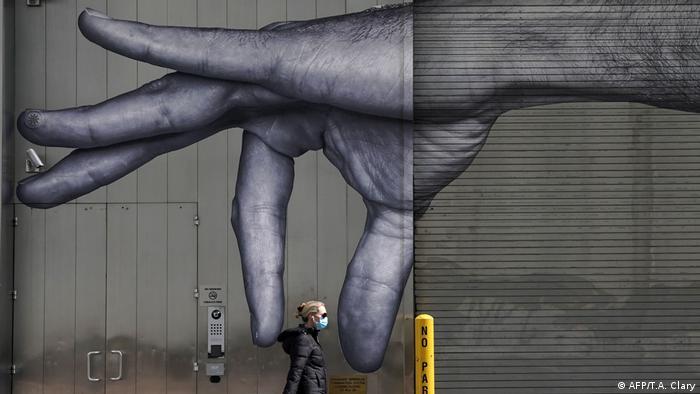 Žena prolazi pored murala na kojem je naslikana ogromna ruka i izgleda kao da je hvata sa dva prsta