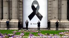 23.04.2020, Spanien, Madrid: Jose Luis Martinez Almeida (3.v.r), Bürgermeister von Madrid, applaudiert nach einer Schweigeminute mit anderen politischen Vertretern vor einer schwarzen Schleife, die an der Puerta de Alcala in Madrid zum Gedenken an die an Covid-19 gestorbenen Menschen angebracht wurde. Foto: Óscar Cañas/Europa Press/dpa +++ dpa-Bildfunk +++