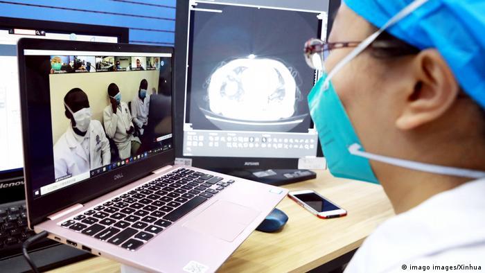 Eine Person in Schutzkleidung sitzt vor einem Laptop und sprocht per Videoanruf mit Personen in Kenia