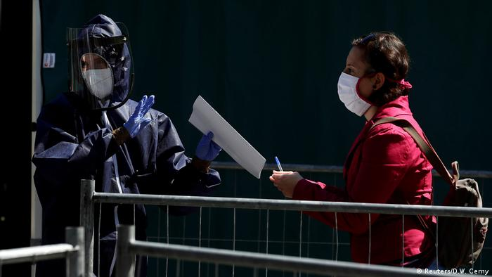A masked medical worker gathers information from a woman who wants to be tested for the coronavirus