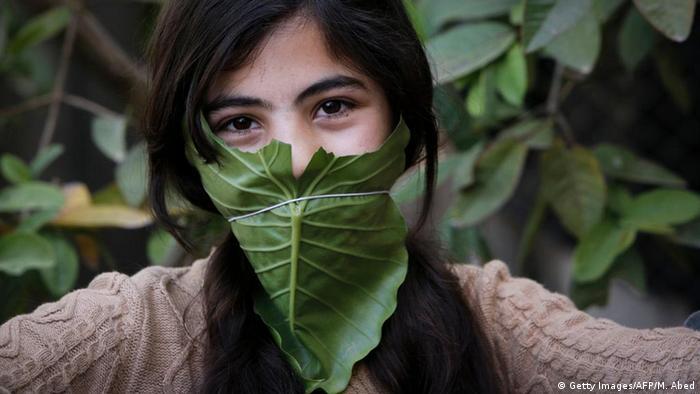 Mädchen mit Blatt vorm Mund: Coronavirus Mundschutz selbst gemacht (Getty Images/AFP/M. Abed)