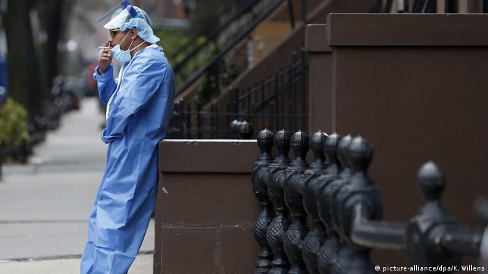 Ein Krankenpfleger in Schutzkleidung raucht