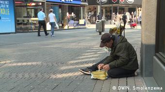 Бездомный в Кельне ест из картонной коробки