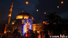 TOPSHOT - People release sky lanterns as they celebrate the start of the Muslim holy month of Ramadan, outside a mosque in Lebanon's southern city of Sidon after sunset on April 23, 2020. (Photo by Mahmoud ZAYYAT / AFP)