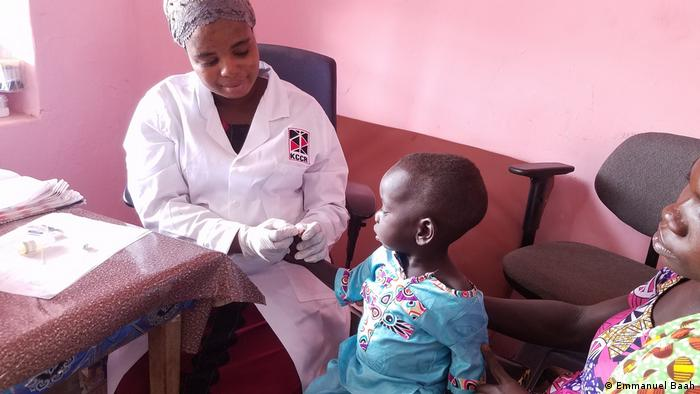 A nurse examines a child in a hospital in Ghana