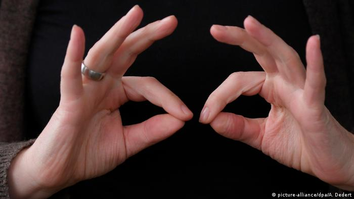 A woman's hands before a black background, forefingers and thumbs rounded in a circle.
