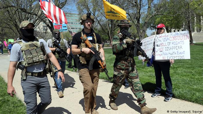 Anti-lockdown protesters walking through Topeka, Kansas with firearms