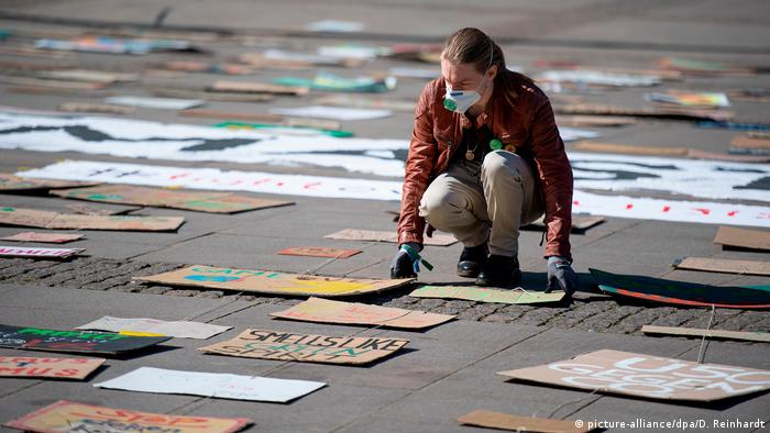 A masked climate activist in Hamburg lays out signs on the ground, alone