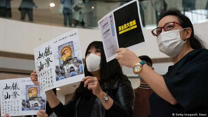 Protesters wears face masks and hold placards during a rally in Hong Kong