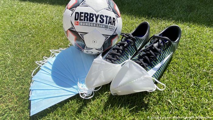 صورة رمزية لكرة القدم والأحذية في ظل كورونا مع فرض ارتداء الكمامة