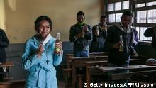 Students drink from bottles of Covid Organics, a herbal tea, touted by Madagascar President Andry Rajoelina as a powerful remedy against the COVID-19 coronavirus, that the authorities gave each student and encouraged them to drink it before the start of classes at the J.J. Rabearivelo High School in downtown Antananarivo on April 23 2020. (Photo by RIJASOLO / AFP) (Photo by RIJASOLO/AFP via Getty Images)