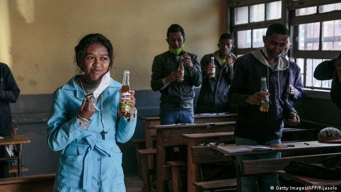 Students drink from bottles of COVID organics, touted by Madagascar's President Rajoelina as a powerful remedy against COVID-19 despite no scientific proof