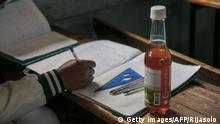 A bottle of Covid Organics, a herbal tea, touted by Madagascar President Andry Rajoelina as a powerful remedy against the COVID-19 coronavirus, that the authorities gave each student and encouraged them to drink it before the start of classes is seen on a student's desk at the J.J. Rabearivelo High School in downtown Antananarivo on April 23 2020. (Photo by RIJASOLO / AFP) (Photo by RIJASOLO/AFP via Getty Images)
