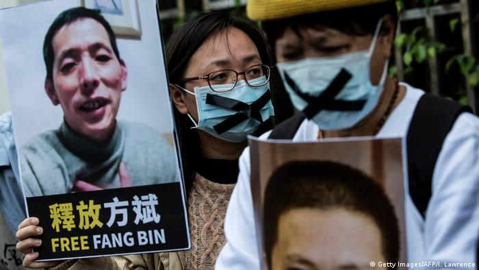 A pro-democracy activist (C) from HK Alliance holds a placard of missing citizen journalist Fang Bin