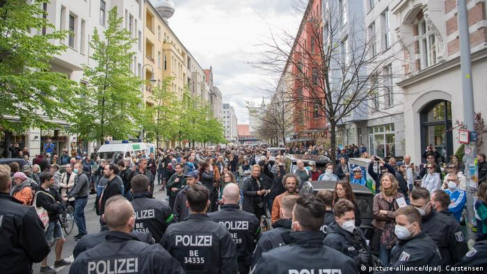 Police stand before a large crowd of people protesting coronavirus restrictions in Berlin