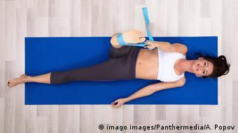Eine Frau auf einer blauen Yoga-Matte macht eine Übung im Liegen