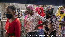 In this photo taken Saturday, April 25, 2020, Ndyeye Fatou, center, the daughter of Bara Tambedou, wears a patterned face mask as she queues to buy bread for her family on the first day of the Muslim fasting month of Ramadan, in Dakar, Senegal. This year the family is celebrating Ramadan at home, with prohibitions on public gatherings and a dusk-to-dawn curfew in place to curb the spread of the new coronavirus. (AP Photo/Sylvain Cherkaoui) |