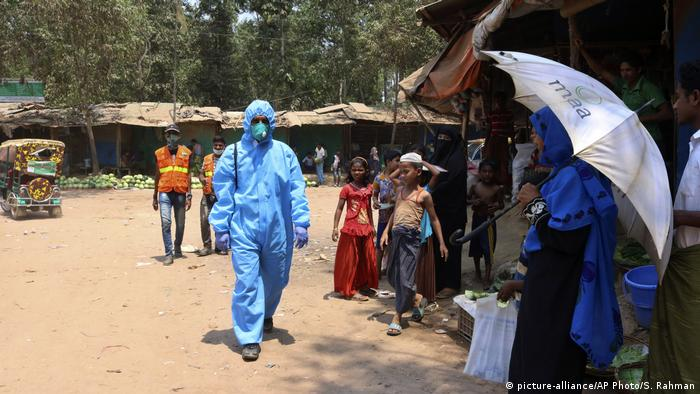 Homem de roupa protetora azul anda entre pessoas em campo de refugiados em Bangladesh