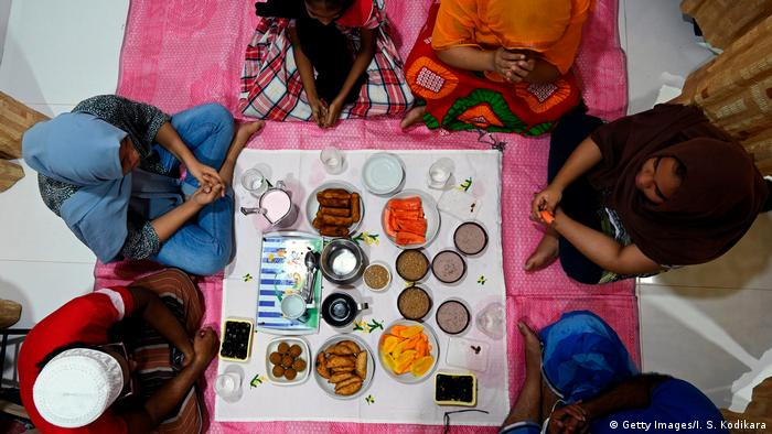 A Muslim family prays before breaking their fast at a home during the Islamic holy month of Ramadan