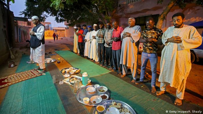 Sudanese men gather in prayers in a street in the capital Khartoum after breaking their fast during the Muslim holy month of Ramadan on April 25, 2020.