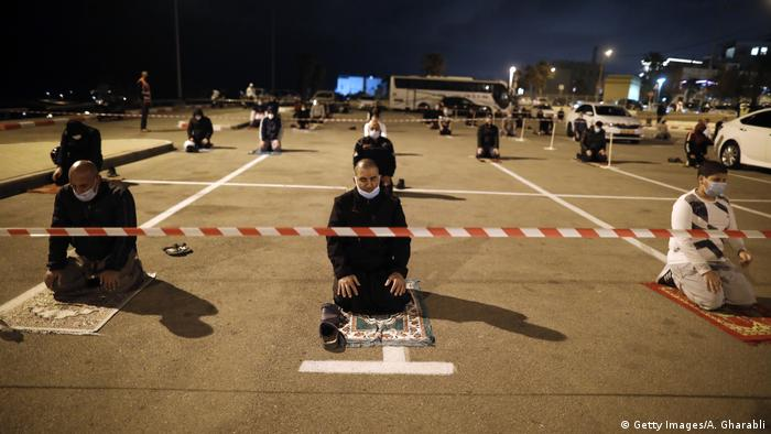 A group of men keep a 2-meter distance amid the COVID-19 pandemic, as they pray in a parking lot near the beach in Jaffa, near the Israeli coastal city of Tel Aviv
