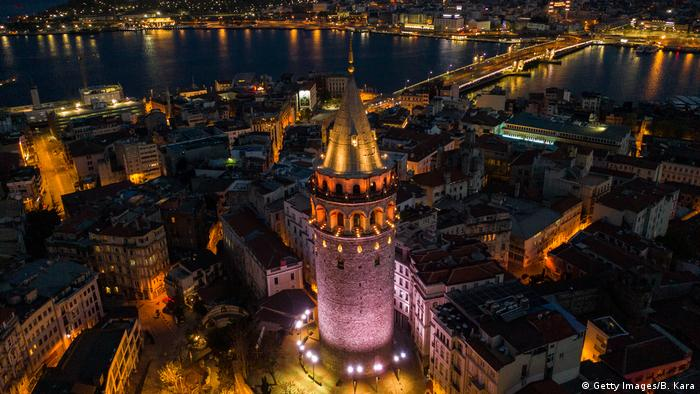 In this aerial photo from a drone, the illuminated roads and square around Istanbul's famous Galata Tower are seen empty