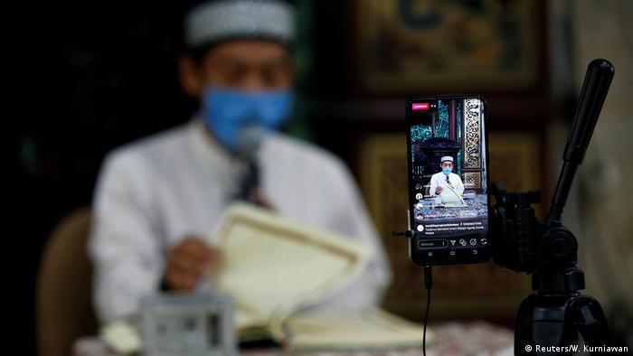 Bambang Suprianto, an Imam wearing a COVID-19 protective mask, reads the Quran which is being streamed through social media