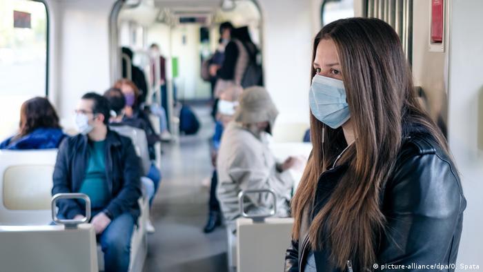 Mulher com máscara protetora em vagão de trem
