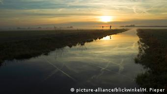 Sunset reflected in the waters of a canal running through moorland in Lower Saxony