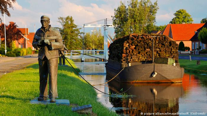 Statue of a worker pulling a peat barge along a canal