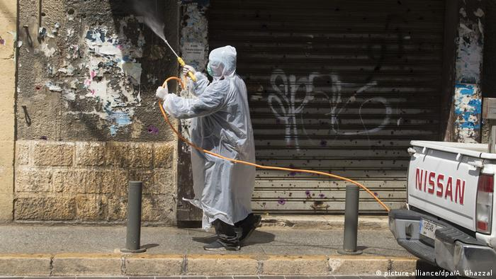 A worker dressed in protective clothing disinfects a building in Beirut after a case of COVID-19