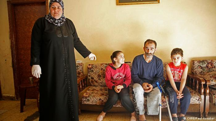 A woman in Lebanon stands beside her seated husband and two children