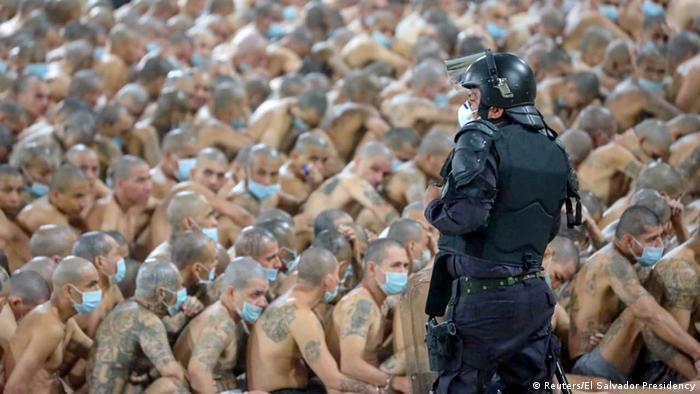 Cientos de presos en una cárcel de El Salvador, sentados en el suelo.