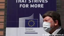 FILE PHOTO: A man wearing a face mask walks past the European Commission headquarters as the spread of coronavirus disease (COVID-19) continues in Brussels, Belgium April 9, 2020. REUTERS/Yves Herman/File Photo