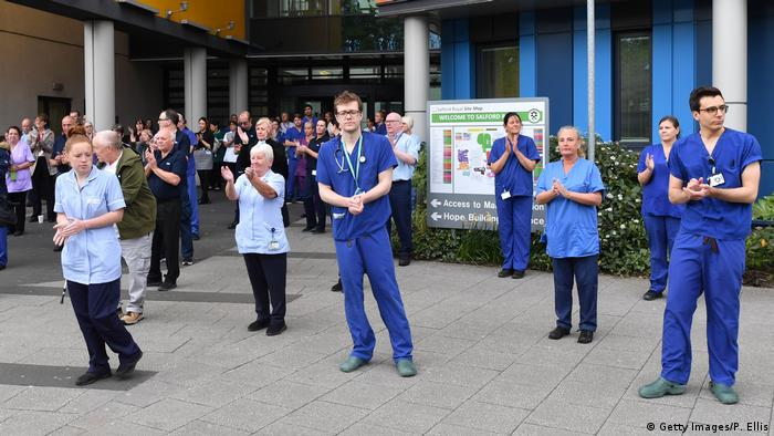 NHS staff applaud after pausing for a minute's silence to honor UK key workers, including NHS staff, health and social care workers, who have died during the coronavirus outbreak