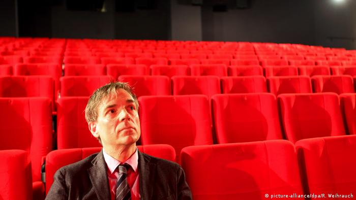 Lars Henrik Gass sitzt in einem leeren Kinosaal