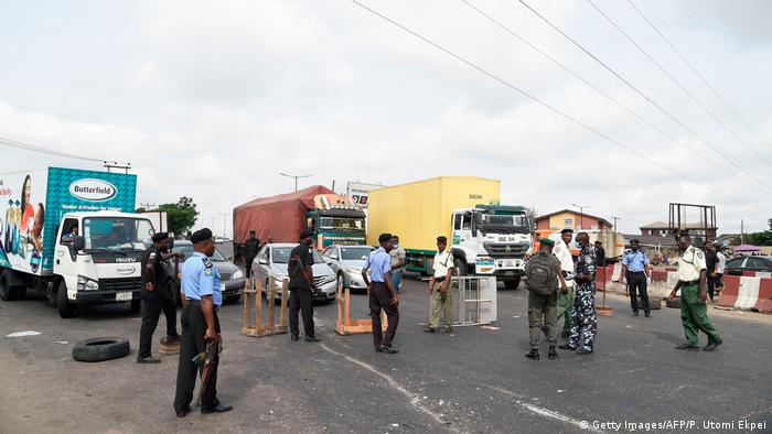 Policemen block the expressway to prevent motorists from driving into Lagos during coronavirus pandemic