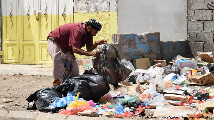 A man looks for recyclable items for selling at a rubbish dump in the southern port city of Aden, Yemen