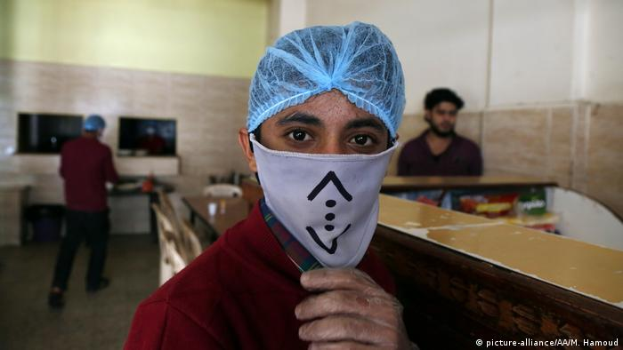 A worker in a shop in Yemen wears a face mask as a precaution against the global coronavirus pandemic