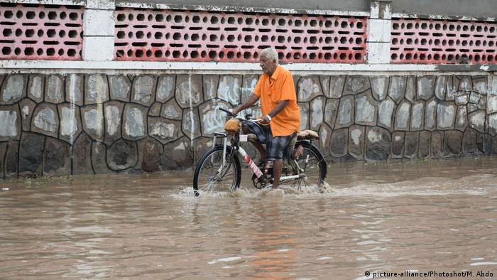 A man rides his bicycle through a waterlogged road in the southern port city of Aden, Yemen