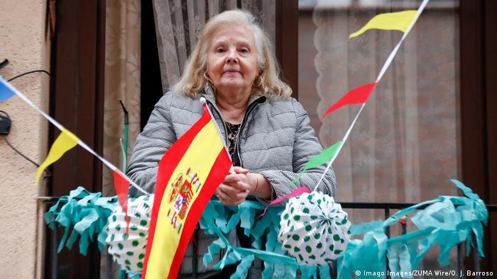Женщина на балконе не выходит из дома из-за карантина в Испании в связи с коронавирусом