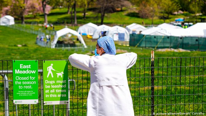 Pessoa com máscara e roupas de enfermagem parada em cerca olhando acampamento