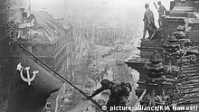 Soldados soviéticos hasteiam bandeira após queda do Reichstag